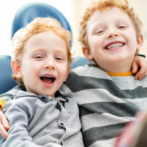 Two young boys laughing and smiling for the camera because their teeth are healthy thanks to our tips on how to fight cavities.