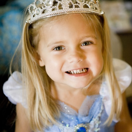 Girl dressed as a princess and wearing a crown after receiving a crown on her tooth which is part of our restorative dentistry for kids in Carmel, Indiana