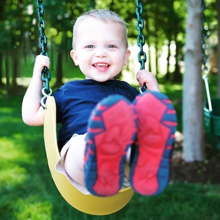 Boy playing on a swing after getting a biopsy before his dental surgery