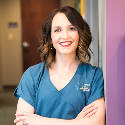 Dr. Juntgen, a Carmel pediatric dentist, leaning against a wall and smiling in her scrubs.