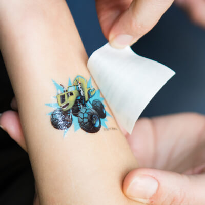 A child's arm with a temporary truck tattoo to show that we offer kid friendly Pediatric Dentistry in Carmel