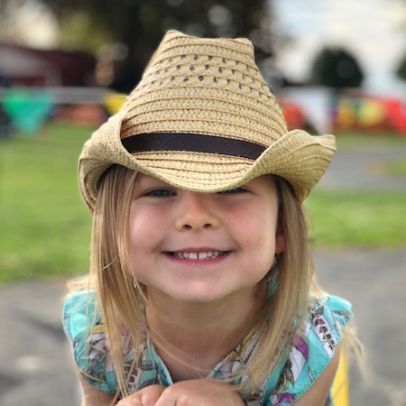 Adorable little girl in a cowboy hat smiling because our pulp therapy restorative dentistry for kids in Carmel, Indiana will restore the health of her teeth