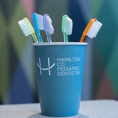 Colorful toothbrushes inside a mug with the hamilton County Pediatric Dentistry logo on it.