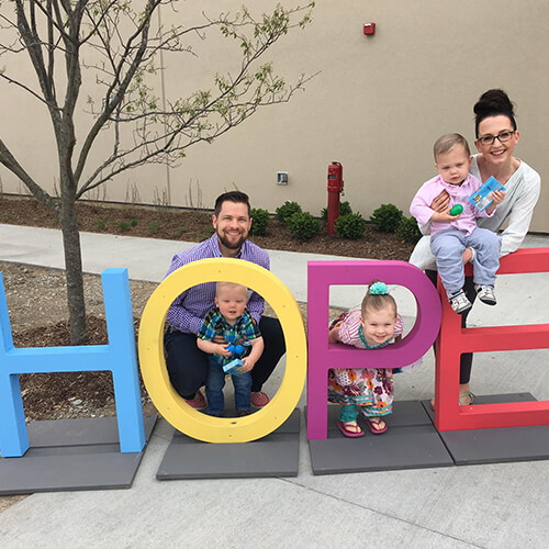 Dr. Juntgen, a Carmel pediatric dentist, with her husband and three small children posing by a giant word %22HOPE%22