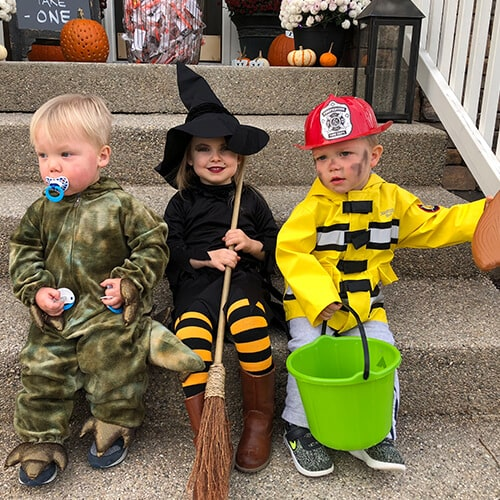 Three adorable little children in Halloween costumes sitting on the front steps of this Carmel pediatric dentist office.
