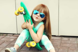 A young girl looking cool in sunglasses and holding a skate board as she learns ways to fight cavities.
